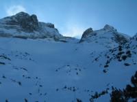 Blick von «Auf den Bänken» durch den Rachen hinauf zum Gipfel, welcher gerade von Schneefahnen umhüllt wird.